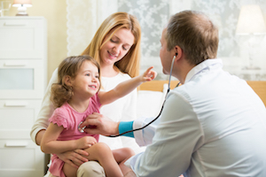 pediatrician talking to mother with a young girl on her lap