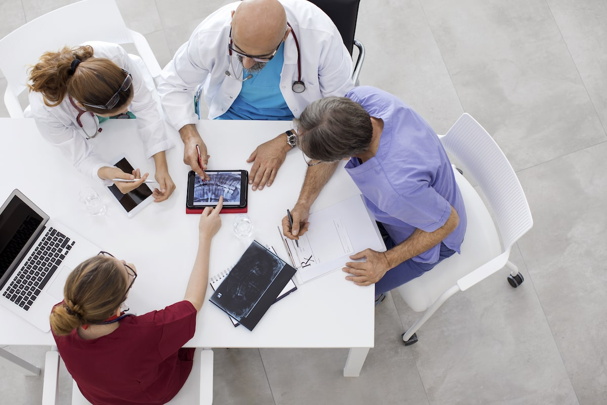 4 doctors and nurses sitting at a table looking at an ipad