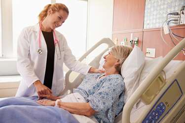 woman hospitalist physician examining woman patient in hospital bed