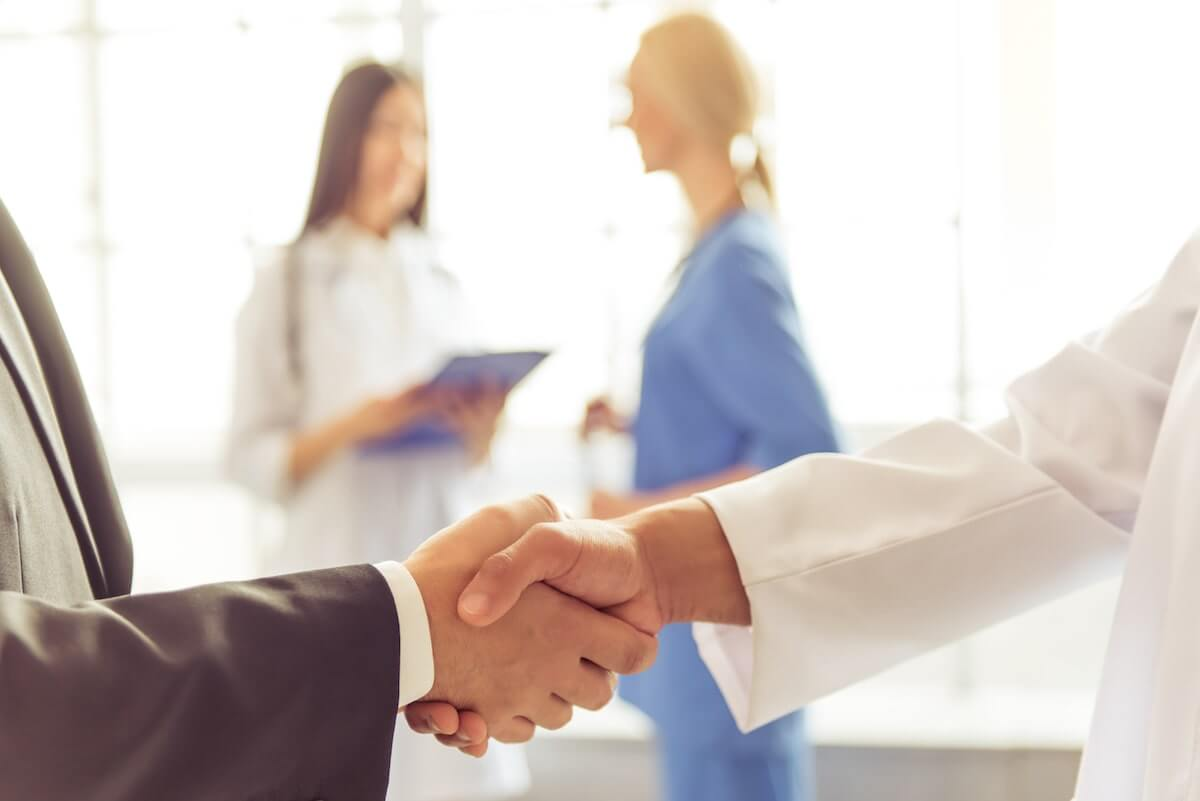 Doctor and hospital administrator shaking hands in hallway