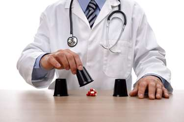 Doctor in a white coat playing a shell game with pills