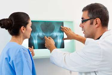 Anesthesiologist and physician discussing a hip fracture x-ray